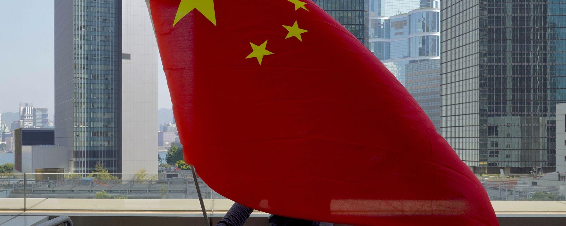 Un supporter pro-Cina sventola una bandiera cinese davanti all'Alta Corte di Hong Kong  - Sputnik Italia, 1920, 28.09.2021
