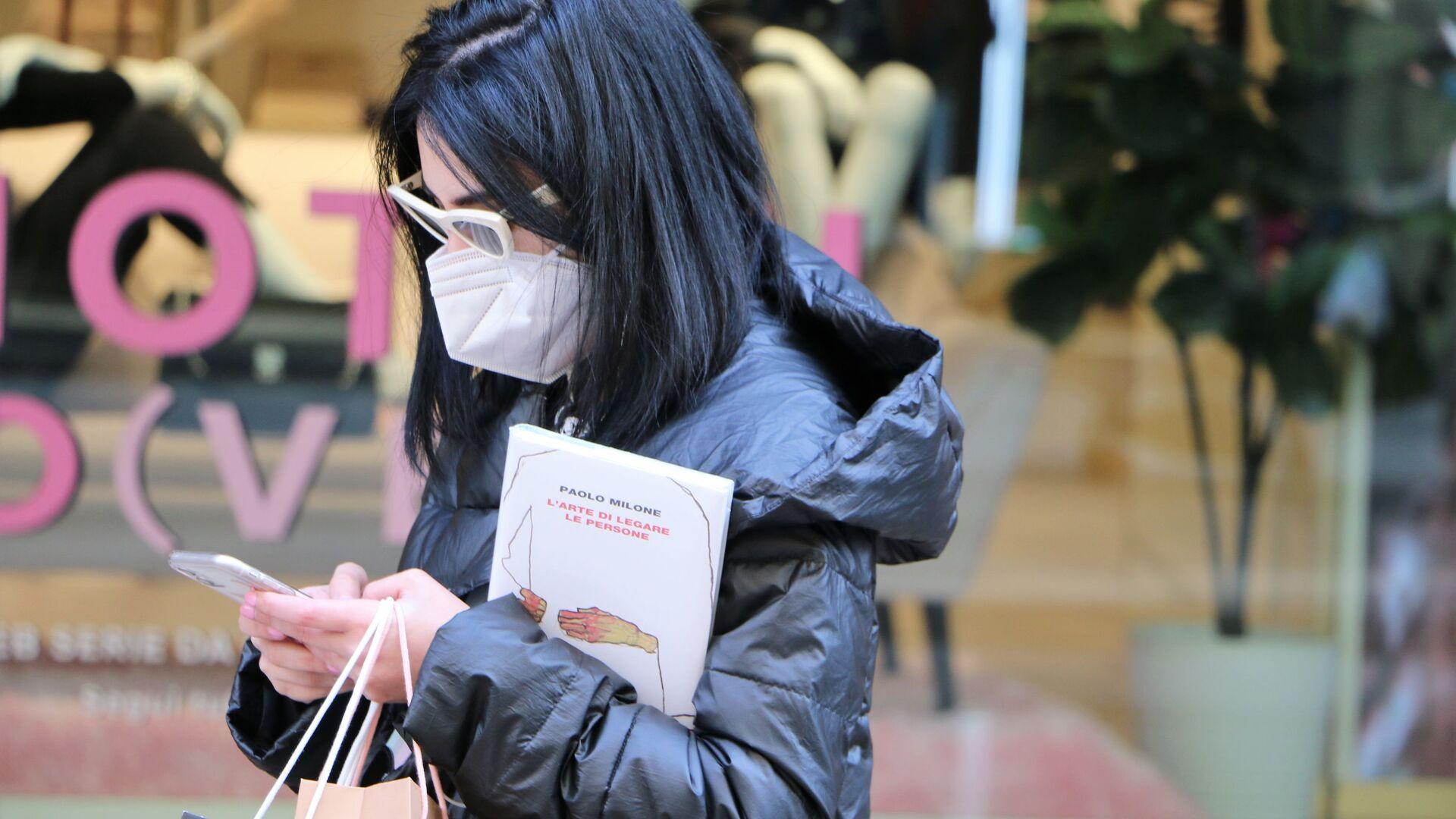 Ragazza in una mascherina con il telefono e il libro - Sputnik Italia, 1920, 21.04.2021