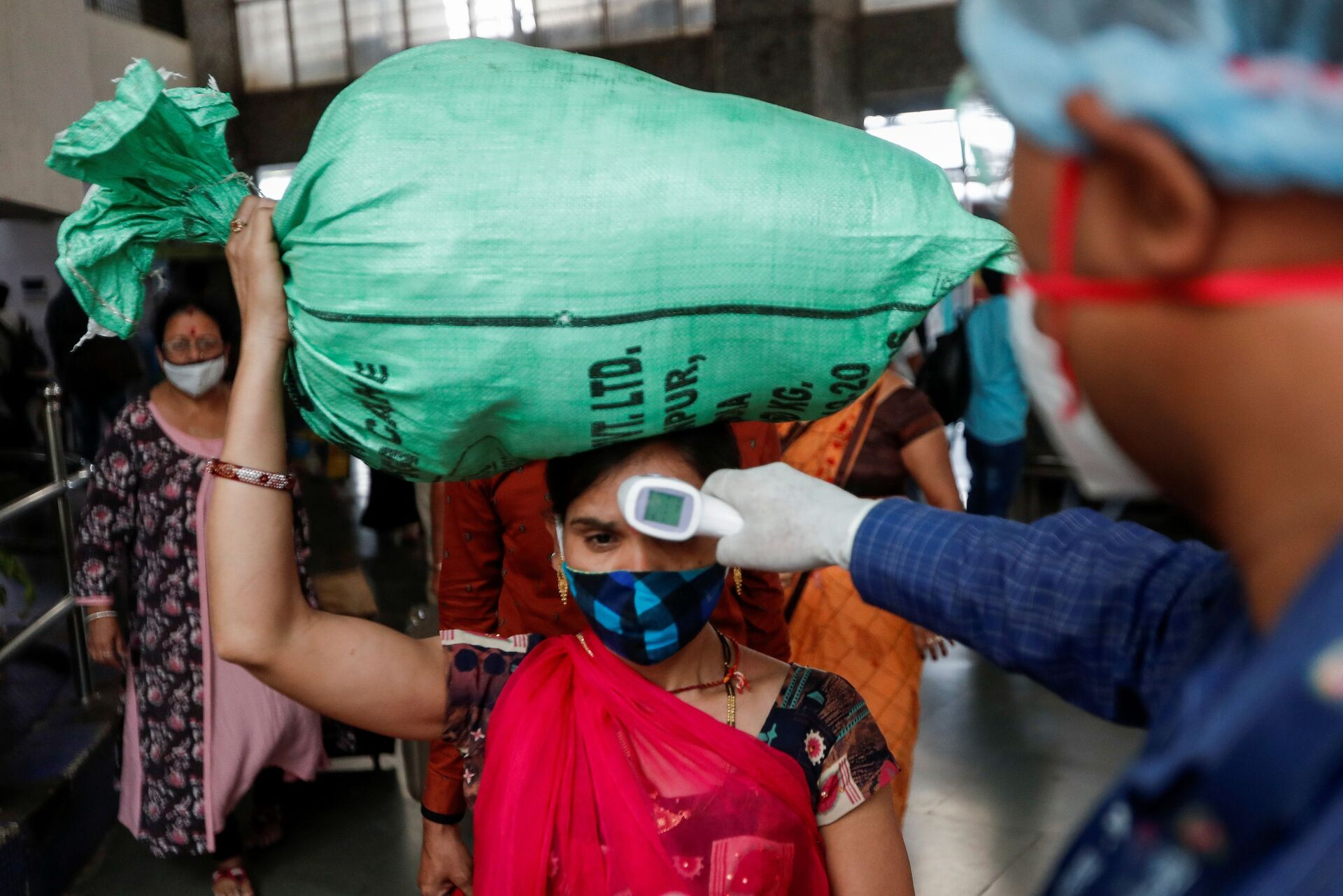 Un'operatore sanitario controlla la temperatura di una passeggera alla stazione di Mumbai, in India - Sputnik Italia, 1920, 18.05.2021