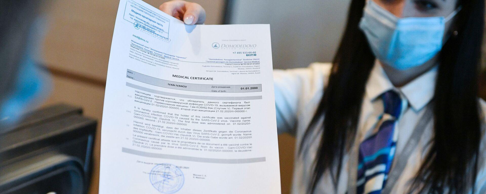 Un'addetta dell'aeroporto di Domodevo consegna ad un passeggero il certificato di vaccinazione in inglese  - Sputnik Italia, 1920, 21.05.2021