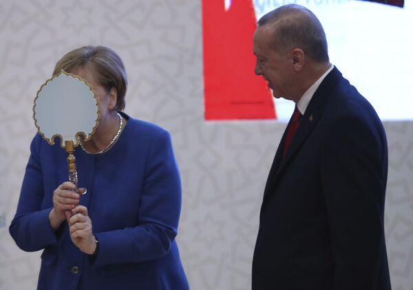 La cancelliera tedesca Angela Merkel scherza mentre riceve uno specchio presentato dal presidente turco Recep Tayyip Erdogan durante la cerimonia di apertura del nuovo campus di un'università turco-tedesca, a Istanbul, venerdì 24 gennaio 2020 - Sputnik Italia