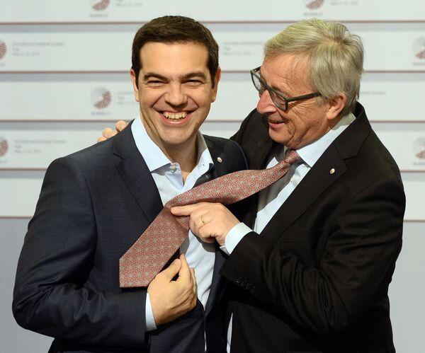 Il primo ministro greco Alexis Tsipras e il presidente della Commissione europea Jean-Claude Juncker scherzano sulla cravatta nel secondo giorno del vertice dell'Unione europea, il 22 maggio 2015 - Sputnik Italia