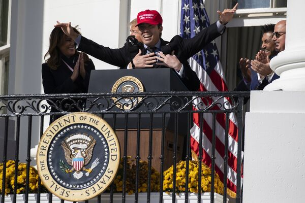 Melania Trump ride mentre l'ex presidente Donald Trump abbraccia il catcher dei Washington Nationals Kurt Suzuki durante un evento per onorare il campione della World Series 2019 alla Casa Bianca, lunedì 4 novembre 2019 - Sputnik Italia