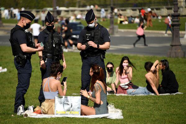 Gli agenti di polizia controllano le persone che si godono una soleggiata giornata primaverile sull'erba di fronte all'Hotel des Invalides a Parigi, il 31 marzo 2021 - Sputnik Italia