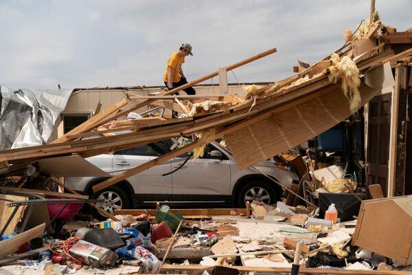 Nathan Mason valuta i danni alla casa di sua nonna il giorno dopo che una serie di tornado ha colpito città di Ohatchee, USA, il 26 marzo 2021 - Sputnik Italia