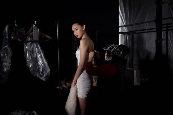 Una modella si prepara per la sfilata durante la China Fashion Week a Pechino, il 28 marzo 2021 - Sputnik Italia