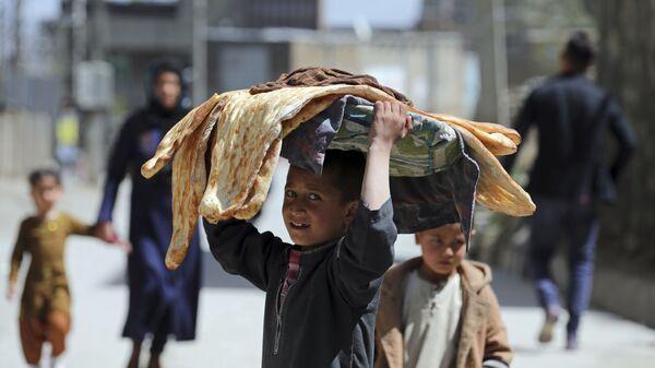 Мальчик с хлебом на голове на одной из улиц Кабула, Афганистан - Sputnik Italia