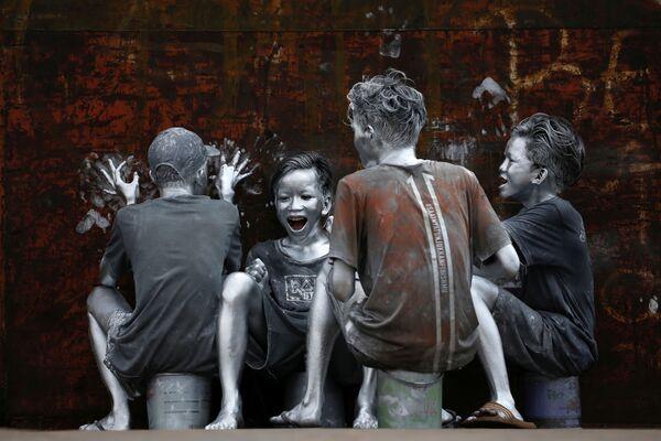 I giovani, che si sono ricoperti dalla testa ai piedi di in argento per diventare 'manusia silver' (silvermen) a Jakarta, Indonesia, il 31 marzo 2021 - Sputnik Italia