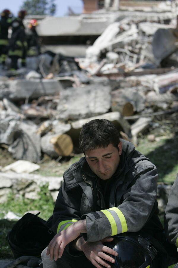 Un vigile del fuoco vicino al luogo crollò un edificio di quattro piani, a L'Aquila, Italia centrale, lunedì 6 aprile 2009 - Sputnik Italia