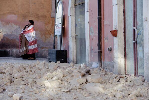 Una coppia tra le macerie dopo il terremoto dell'Aquila, il 6 aprile 2009  - Sputnik Italia