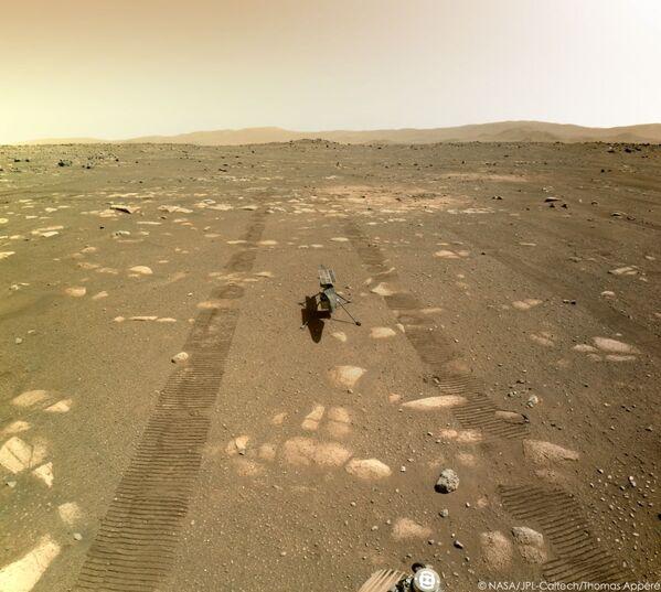 Nello scatto si vede il suolo marziano con la tipica colorazione rossastra, ricco di rocce, intorno al rover - Sputnik Italia