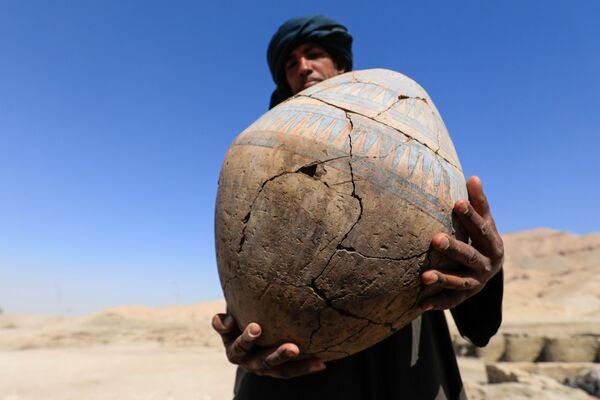 Una persona prende un oggetto scoperto a Città d'oro perduta'', che è stata recentemente scoperta dagli archeologi, nella Cisgiordania di Luxor, nell'Alto Egitto, il 10 aprile 2021 - Sputnik Italia