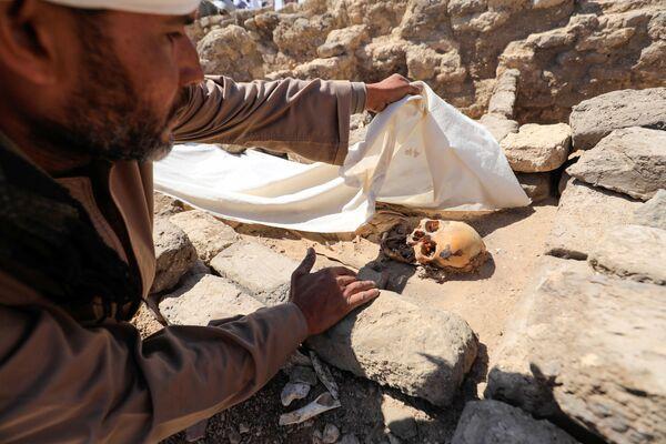 Un uomo guarda i resti umani scheletrici nella Città d'oro perduta'', che è stata recentemente scoperta dagli archeologi, nei pressi di Luxor, nell'Alto Egitto, il 10 aprile 2021 - Sputnik Italia