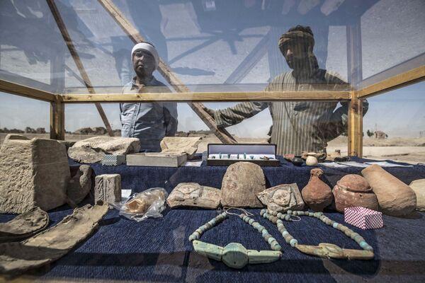 I lavoratori guardano un'esposizione di manufatti scoperti - Sputnik Italia