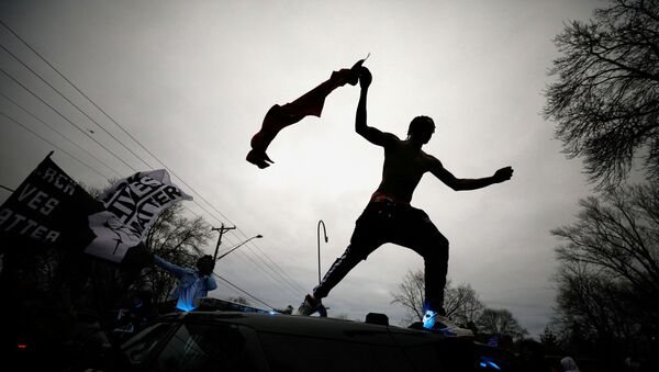 A demonstrator jumps off a police cruiser during a protest after police allegedly shot and killed a man, who local media report is identified by the victim's mother as Daunte Wright, in Brooklyn Center, Minnesota, U.S., April 11, 2021. - Sputnik Italia