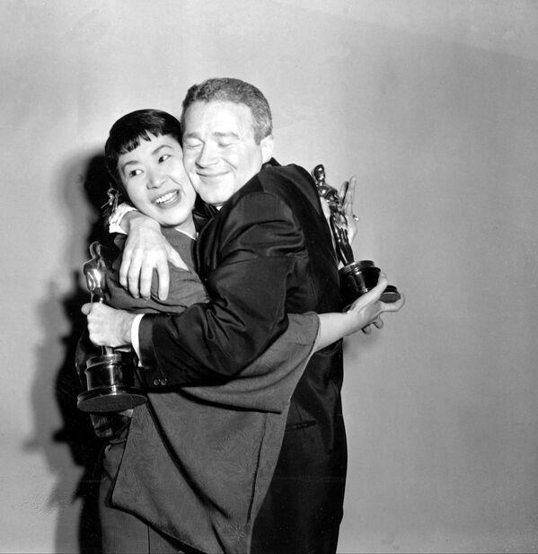 Miyoshi Umeki e Red Buttons si abbracciano durante la Cerimonia di premiazione annuale degli Oscar, il 26 marzo 1958 - Sputnik Italia