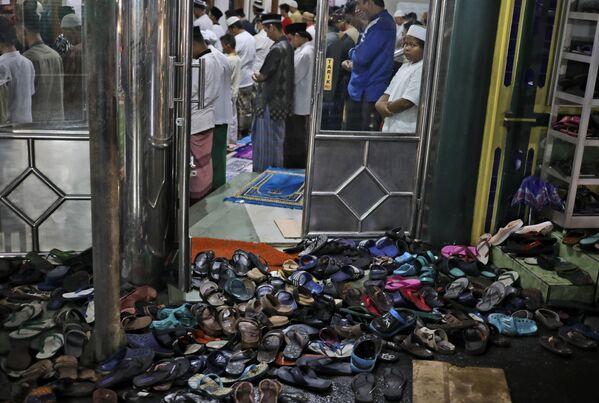 Le calzature vengono lasciate fuori mentre le persone eseguono una preghiera serale del Tarawih durante la prima sera del sacro mese di digiuno del Ramadan, in una moschea a Giacarta, Indonesia, lunedì 12 aprile 2021 - Sputnik Italia