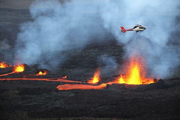 Un elicottero che vola mentre la lava sta eruttando dal vulcano Piton de la Fournaise sull'isola La Riunione, un dipartimento francese nell'Oceano Indiano - Sputnik Italia