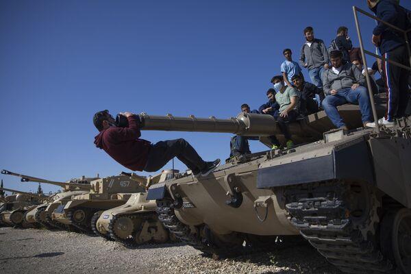 Gli studenti salgono su un carro armato durante una cerimonia che segna l'annuale Giorno della memoria per ricordare i soldati caduti e le vittime del terrore, presso il sito commemorativo del Corpo corazzato israeliano a Latrun, Israele, mercoledì 14 aprile 2021 - Sputnik Italia