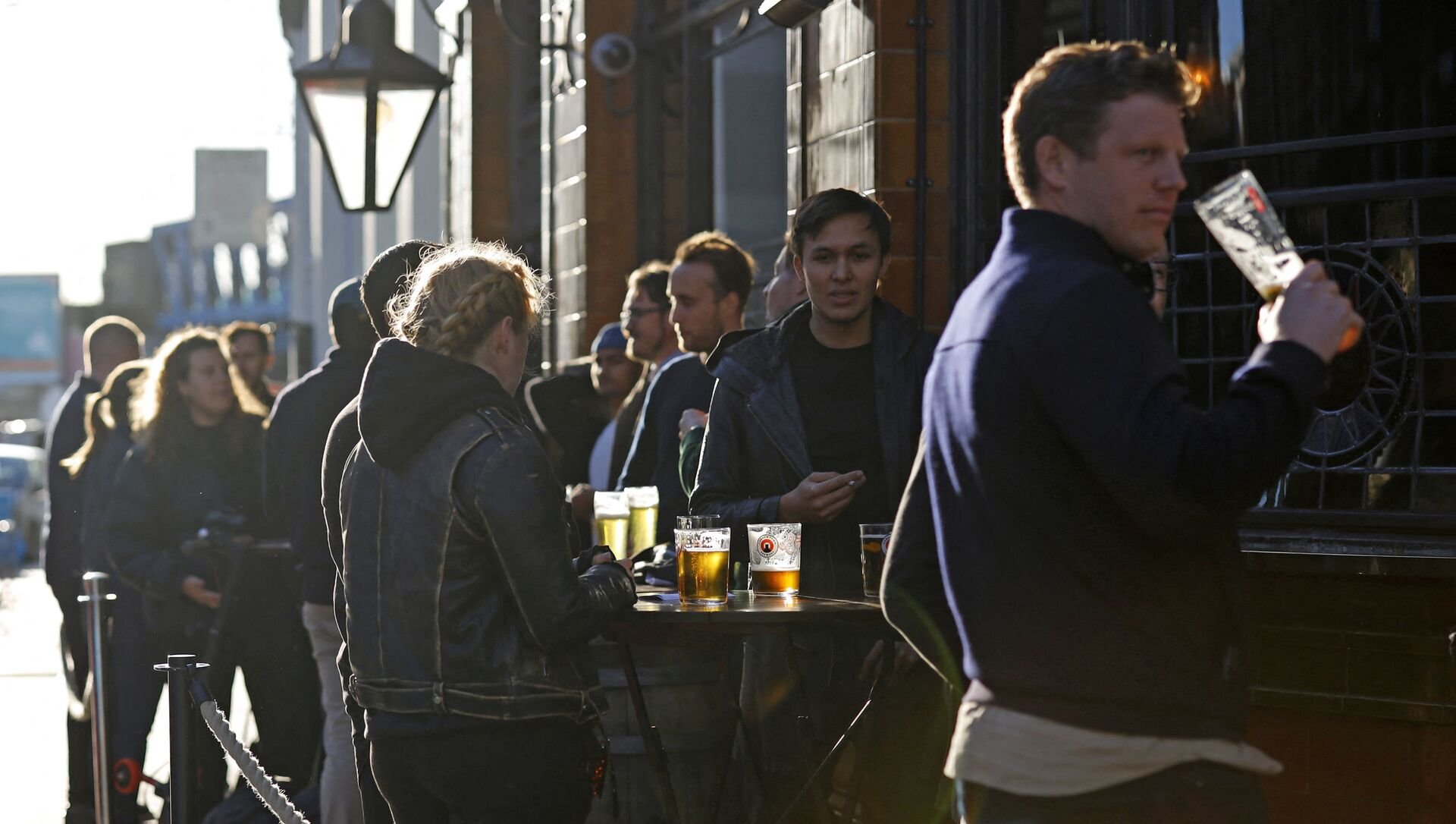After-work drinkers enjoy a pint outside a pub in Borough Market, in London on September 25, 2020, as new earlier closing times for pubs and bars in England and Wales are introduced to combat the spread of the coronavirus. - Sputnik Italia, 1920, 18.04.2021