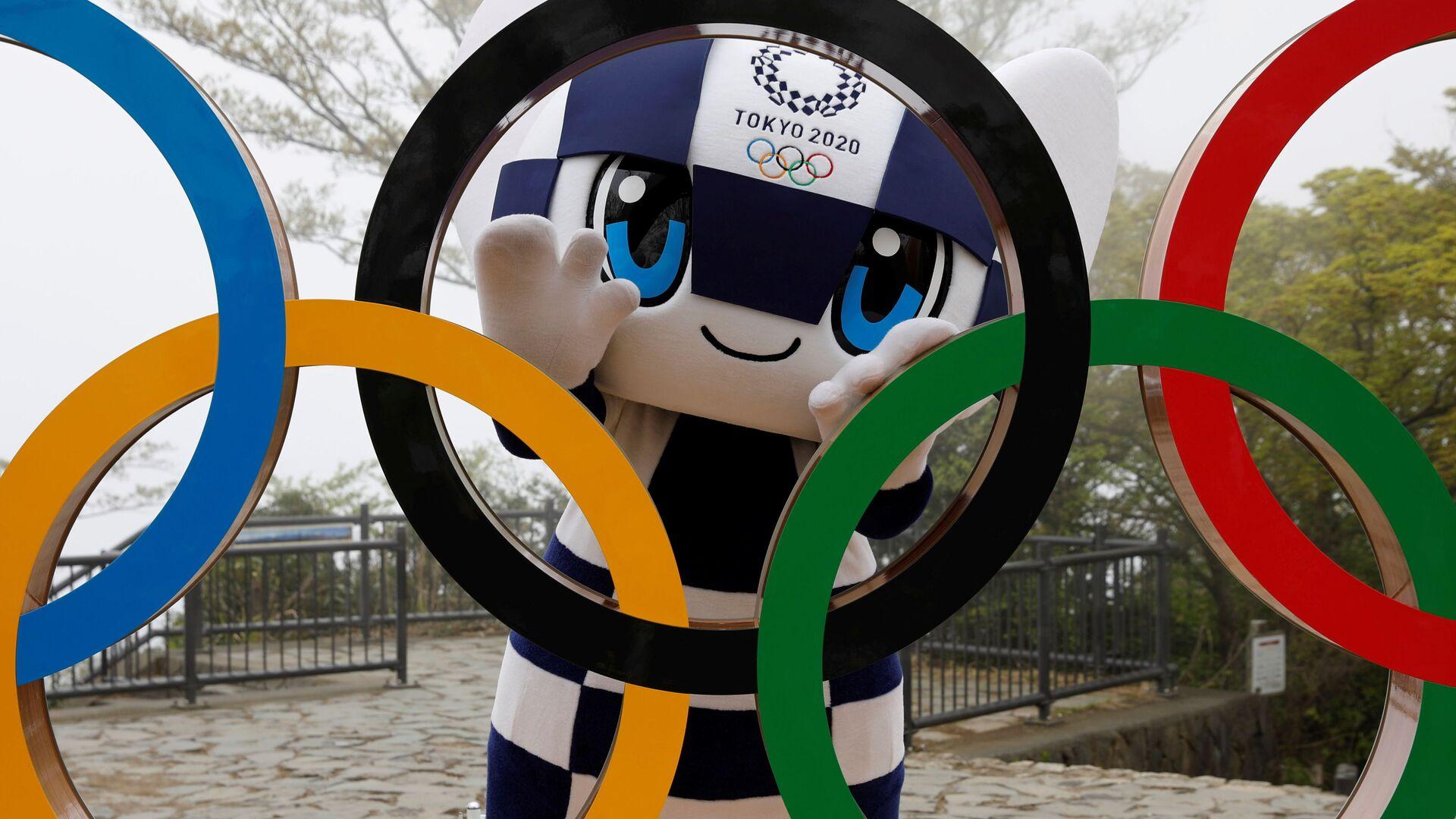 Талисман Летней Олимпиады в Токио Miraitowa позирует сзади Олимпийских колец после мероприятия по случаю 100 дней до Олийписких игр в Токио  - Sputnik Italia, 1920, 25.05.2021