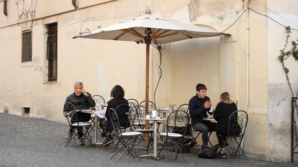 Люди завтракают на открытой веранде бара в Риме - Sputnik Italia