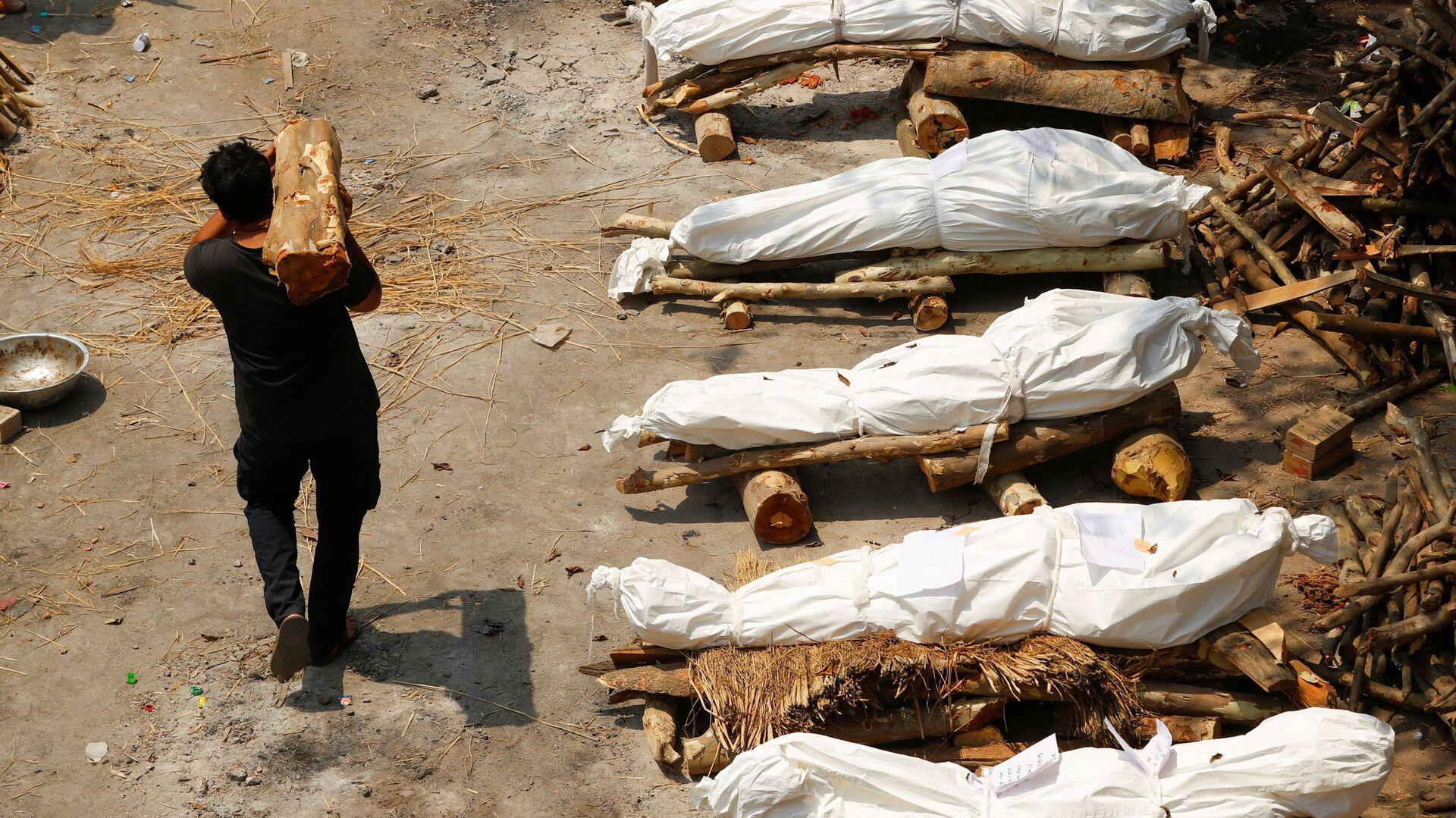 Un uomo con legna da ardere passa davanti alle pire funerarie durante la cremazione di massa in India - Sputnik Italia, 1920, 15.05.2021