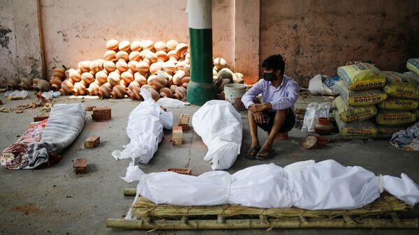 Мужчина сидит рядом с телами умерших от коронавируса перед массовой кремацией в крематории Нью-Дели, Индия - Sputnik Italia