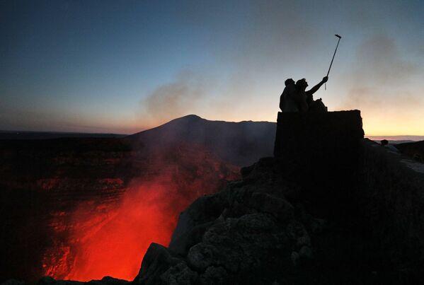 Turisti fanno le foto vicino al cratere del vulcano Masaya nel Parco Nazionale del Nicaragua - Sputnik Italia