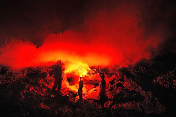 Turisti nella grotta di lava Zvezda nell'area delle aperture del vulcano Tolbachik nella penisola della Kamchatka (Russia) - Sputnik Italia