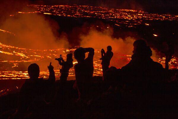 Persone guardano la lava scorrere durante l'eruzione del vulcano nella penisola di Reykjanes, nel sud-ovest dell'Islanda - Sputnik Italia