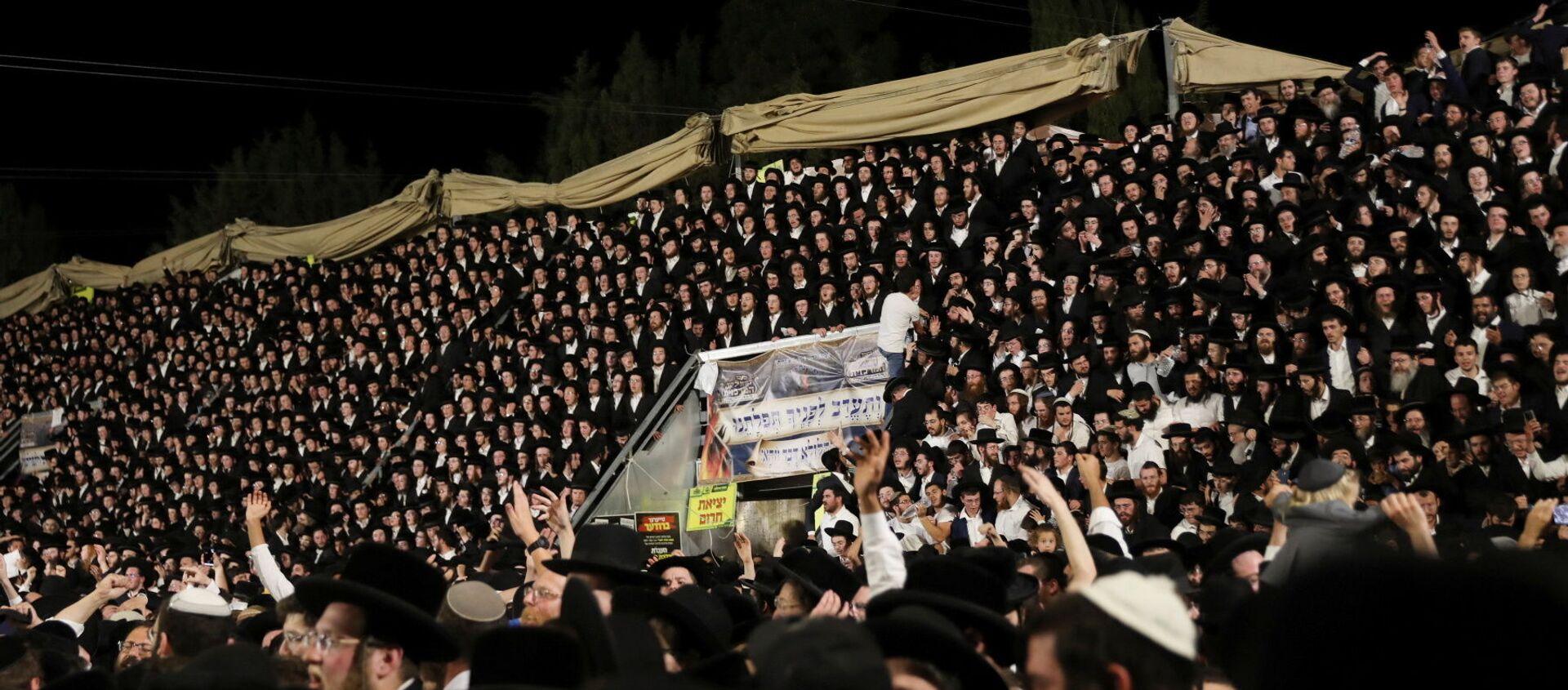 Fedeli ebrei cantano e ballano mentre si trovano sulle tribune all'evento Lag Ba'Omer sul Monte Meron, nel nord di Israele, il 29 aprile 2021. - Sputnik Italia, 1920, 30.04.2021