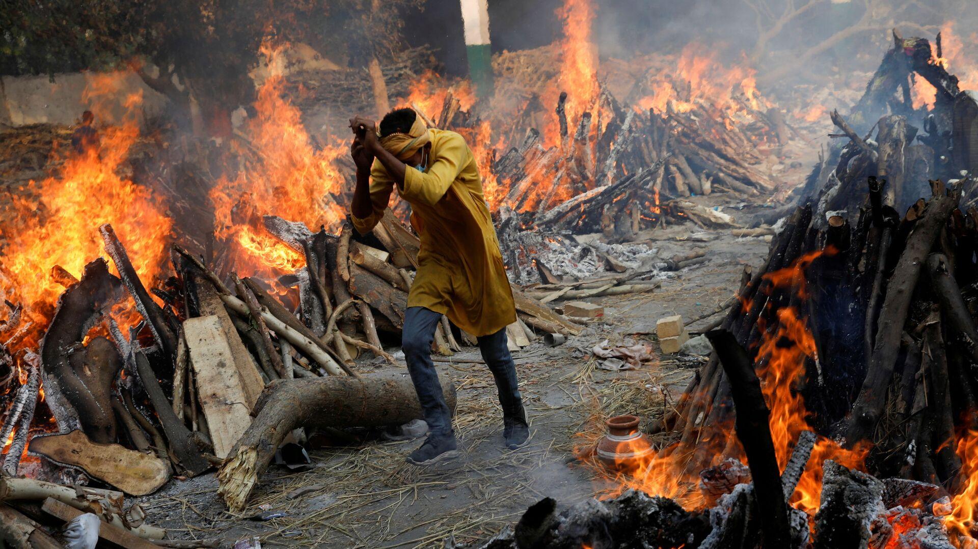 Un uomo passa davanti alle pire funerarie in fiamme dei morti da coronavirus (Covid-19), durante una cremazione di massa, in un crematorio a Nuova Delhi, India 26 aprile 2021.   - Sputnik Italia, 1920, 05.05.2021