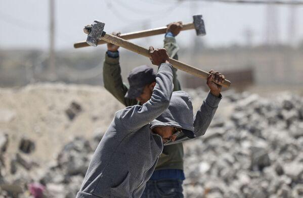 I lavoratori palestinesi rompono le rocce con i martelli in una cava di pietra a Gaza City durante la Giornata internazionale del Lavoro - Sputnik Italia