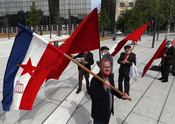Un uomo sventola una vecchia bandiera jugoslava durante una manifestazione in occasione della Giornata internazionale del Lavoro a Belgrado, in Serbia - Sputnik Italia