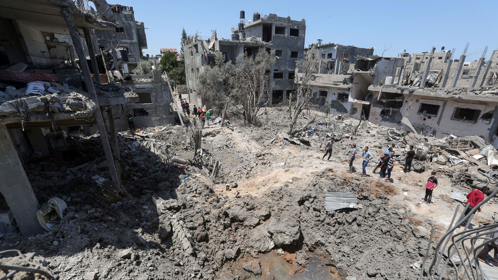 Палестинцы собираются на месте разрушенных домов после израильских авиационных и артиллерийских ударов в секторе Газа - Sputnik Italia, 1920, 30.05.2021