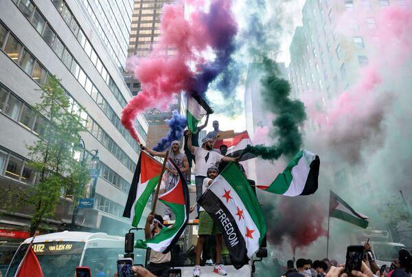 I manifestanti tengono le bandiere della Palestina e della Siria durante una manifestazione a sostegno della Palestina nel centro di Manhattan, New York, USA, il 18 maggio 2021. - Sputnik Italia