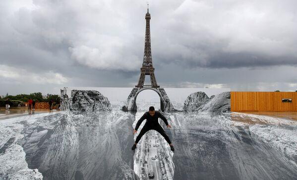 Lo street artist e fotografo conosciuto come JR ha inaugurato una delle sue caratteristiche opere illusionistiche sulla Esplanade Des Droits de l'homme al Trocadero: la Torre Eiffel che si affaccia, come un ponte surreale, su un crepaccio in fondo al quale passa una strada con la città sullo sfondo. - Sputnik Italia