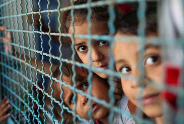 I bambini palestinesi, fuggiti dalle loro case a causa degli attacchi aerei israeliani, guardano attraverso una recinzione di una scuola delle Nazioni Unite per i rifugiati, a Gaza City il 18 maggio 2021. - Sputnik Italia