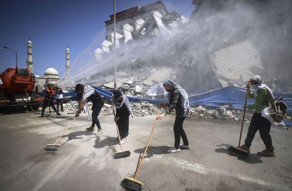Volontari palestinesi e lavoratori municipali rimuovono le macerie dopo che la torre Hanadi a Gaza city si è sbriciolata in pochi attimi, colpita da missili ad alto potenziale sganciati dall'aviazione israeliana, il 25 maggio 2021.  - Sputnik Italia