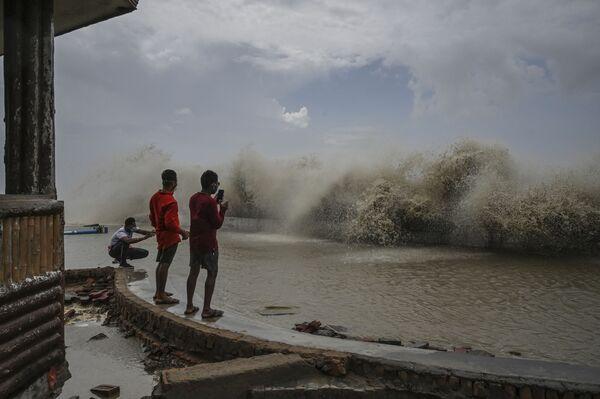 I residenti fotografano le onde che si infrangono su una costa dopo che il ciclone Yaas ha colpito la costa orientale dell'India nel Golfo del Bengala a Digha, a circa 190 km da Calcutta, il 27 maggio 2021. - Sputnik Italia