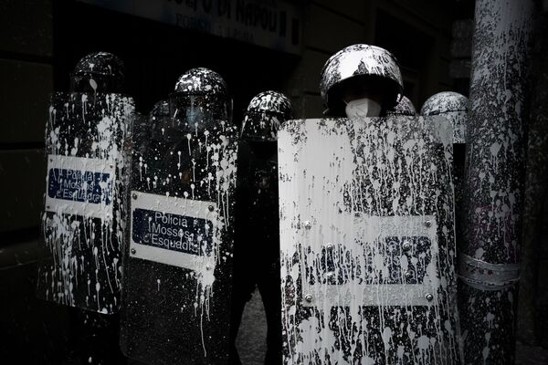 Poliziotti in tenuta antisommossa coperti della vernice usata dai manifestanti per protestare contro lo sfratto del ventottenne Axel Altadill, che dal 2019 è accusato di occupare un appartamento, Barcellona, Spagna, martedì 25 maggio 2021. - Sputnik Italia