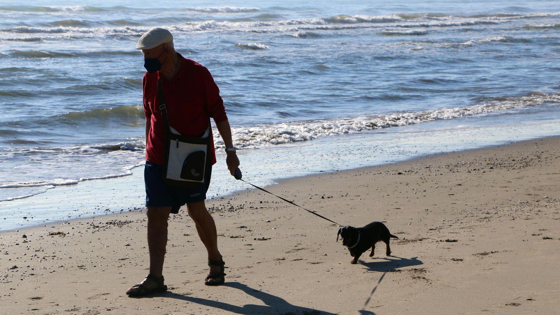 Un uomo con il suo cane passeggia lungo la costa del mare - Sputnik Italia, 1920, 03.06.2021