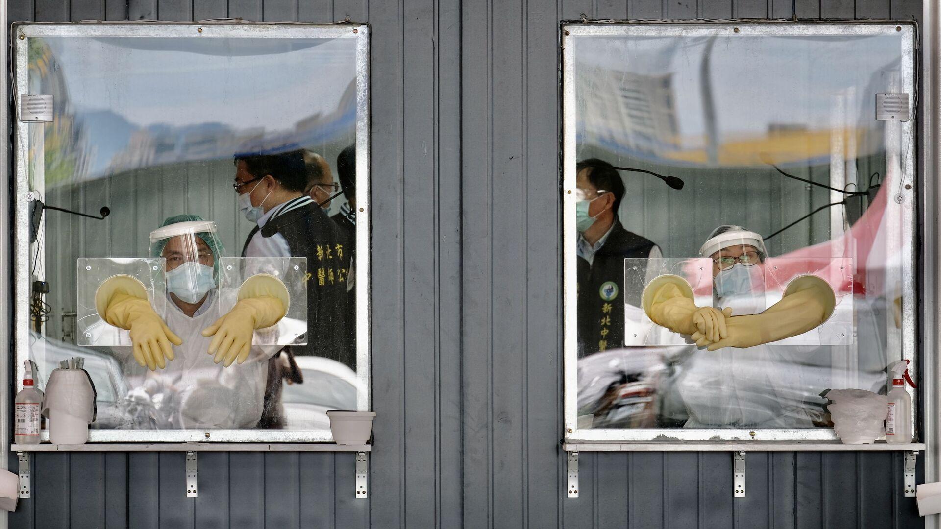 Медицинский персонал в зоне проверки на Covid-19 в Нью-Тайбэе - Sputnik Italia, 1920, 15.06.2021