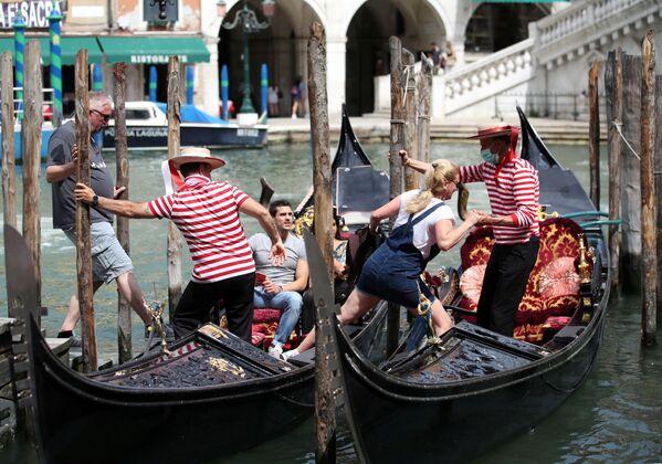 I gondolieri aiutano i turisti a salire sulle gondole. - Sputnik Italia