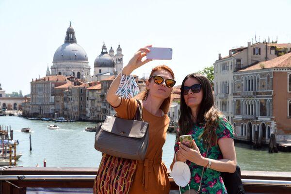 I turisti scattano selfie sul Ponte dell'Accademia, sul Canal Grande a Venezia il 3 giugno 2021. - Sputnik Italia
