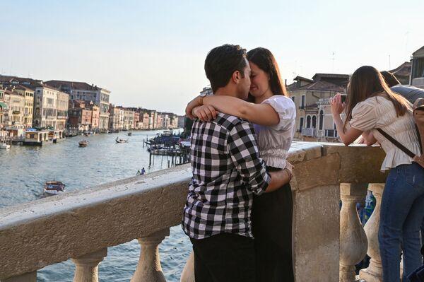 Una coppia si abbraccia sul ponte di Rialto, sul Canal Grande a Venezia. - Sputnik Italia