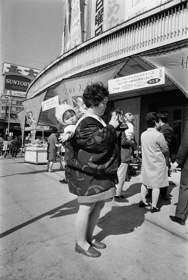 Una persona con addosso il costume tradizionale giapponese scatta una foto dei negozi, Tokyo, 1972. - Sputnik Italia