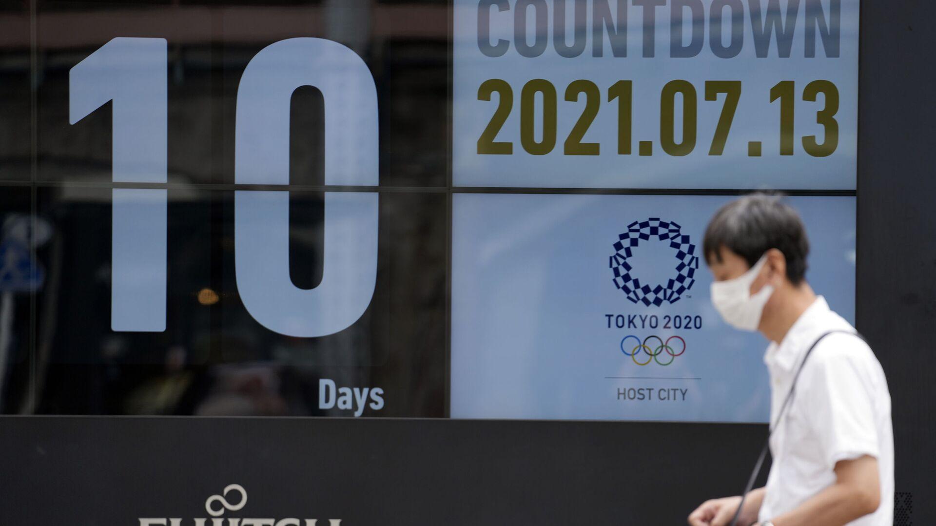 Мужчина в маске напротив календаря обратного отсчета до начала Олимпиады-2002 в Токио  - Sputnik Italia, 1920, 13.07.2021
