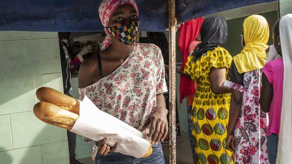 Девушка в маске покупает хлеб для своей семьи в первый день священного для мусульман месяца Рамадан в Дакаре, Сенегал - Sputnik Italia